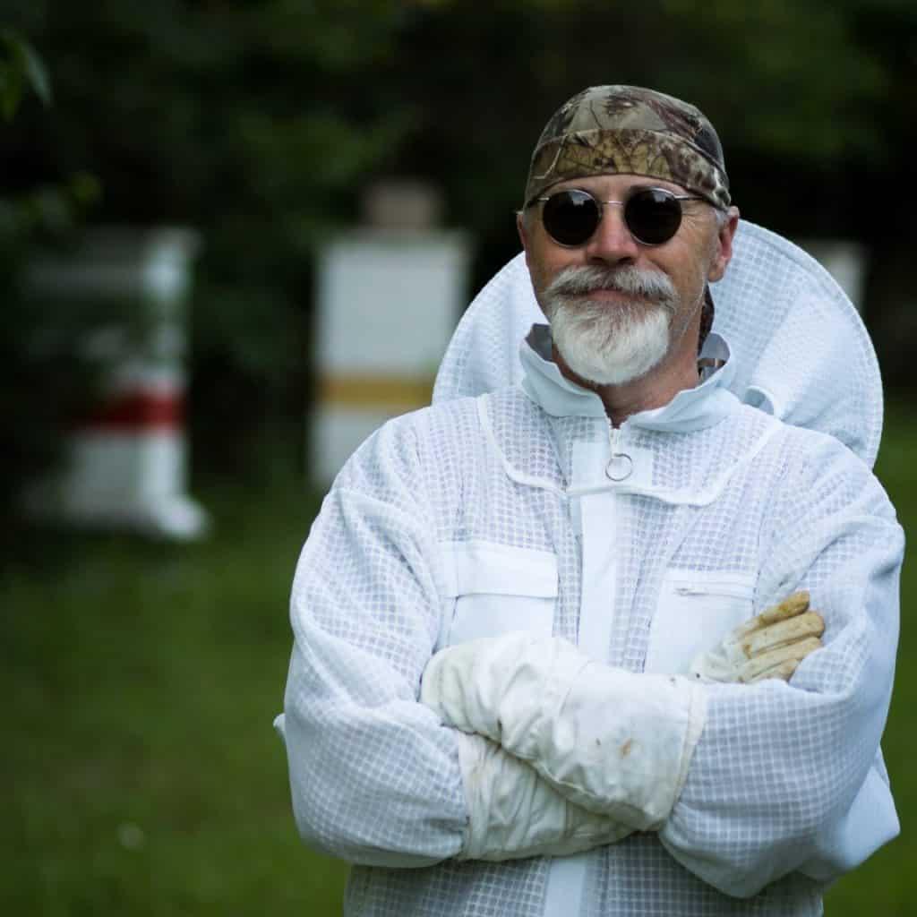 Beekeeper in ventilated suit